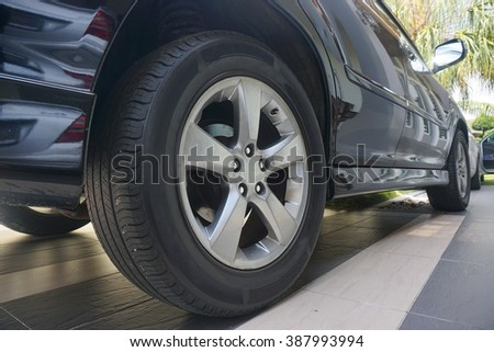Close up of a black car tyre park at home. Black car wit its tyre                           - stock photo