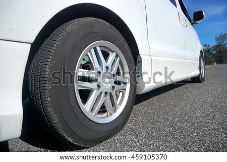 Close up of a black car tyre park on the road