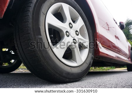 Close up of a black car tyre park on the road. Side view of Red car. View from bottom of the car.