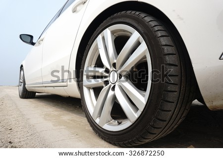 Close up of a black car tyre park on the sand - stock photo