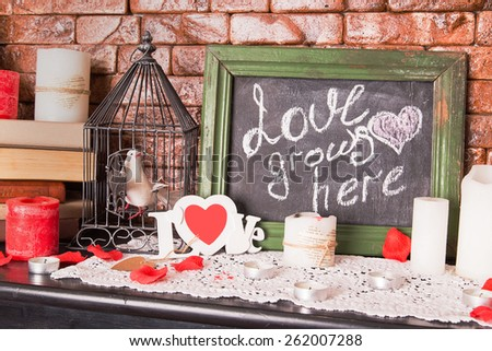 Close up of a black dirty board with the words Love grows here with candles on shelf - stock photo