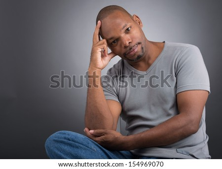Close-up of a black man being in thoughts against a grey background - stock photo