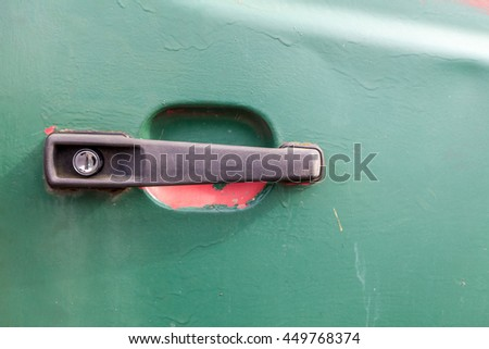 Close up of a black plastic car door handle. The vehicle door is green and there is red underneath the paint. - stock photo