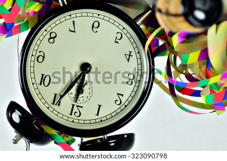 close up of  a black retro alarm clock, around midnight, with paper streamers and cork from a bottle of sparkling wine,  horizontal, slanted, headlong, head first / New Year´s Eve, Head first  - stock photo
