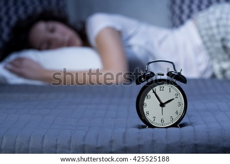 Close-up of a black, vintage alarm clock on a bed where a young woman is lying in the blurry background - stock photo