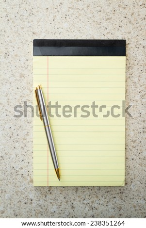 close up of a blank note pad and a pen for a home office concept - stock photo