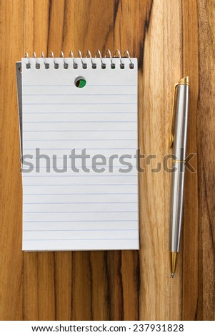 close up of a blank note pad and a pen on a wooden desk for a home office concept - stock photo