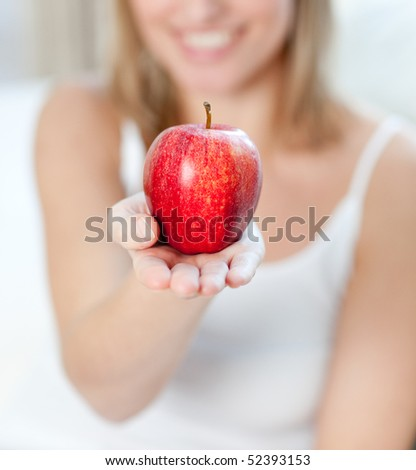 Close-up of a blond woman showing an apple at home