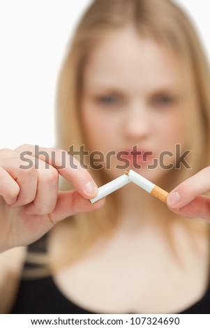 Close up of a blonde-haired woman breaking a cigarette against white background