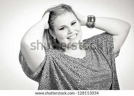 Close up of a Blonde Plus size woman, a model. The woman has her hands in the hair. In black and white. - stock photo