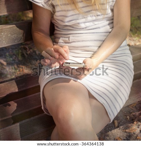 Close up of a blonde woman in white dress sitting alone on the benches in the sunny park and using mobile smart phone.  - stock photo