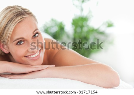 Close up of a blonde woman lying on a lounger in a wellness center - stock photo