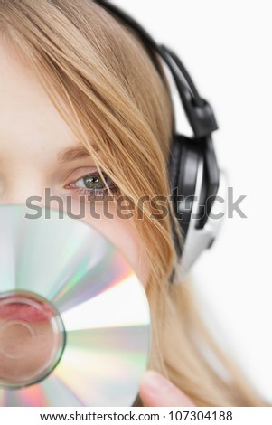 Close up of a blonde woman with a cd in front of her face against a white background - stock photo
