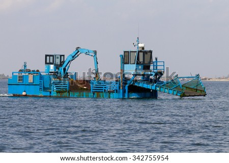 Close up of a blue dredger working on italian Po river lagoon. Industrial vehicle - stock photo