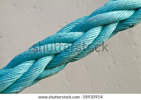 Close up of a blue slightly warn mooring rope under tension against a white background - stock photo