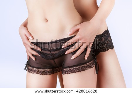 Close-up of a body of two lesbians in black panties on a light background