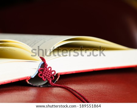 Close up of a book with red woven thread bookmark on red genuine armchair. - stock photo