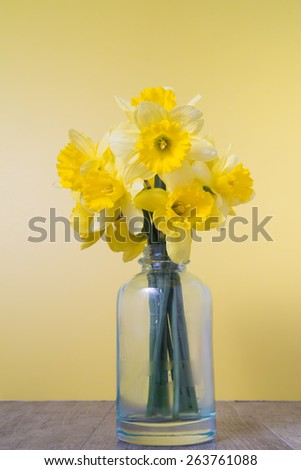 Close up of a bouquet of daffodils in a vintage bottle on a rustic wood table. - stock photo