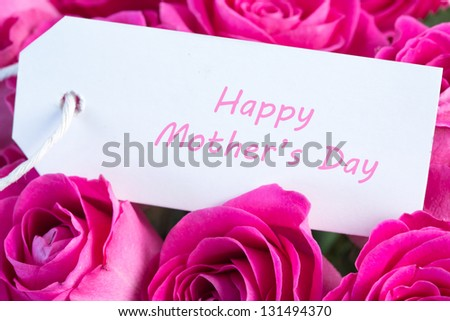 Close-up of a bouquet of pink roses with happy mothers day written in pink on a card - stock photo
