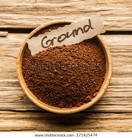 Close up of a bowl full of ground coffee over an old wooden table - stock photo