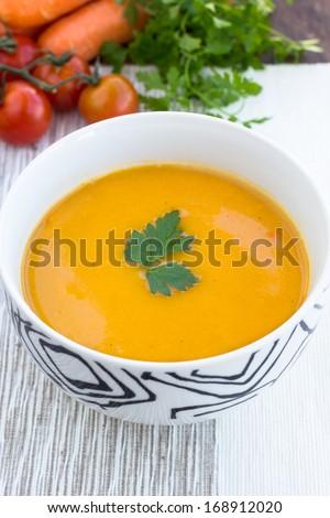 Close up of a bowl of carrot, pumpkin and sweet potato vegetarian soup - stock photo