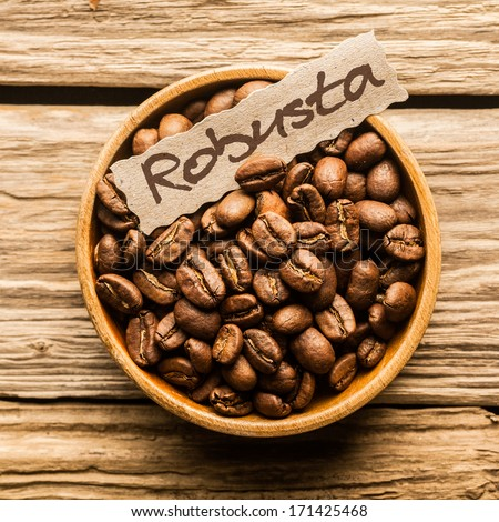 Close up of a bowl of Robusta coffee beans over an old wooden table - stock photo