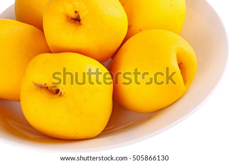 Close-up of a bowl of yellow, ripe fruit of the flowering or Japanese quince (Chaenomeles hybrids) isolated against a white background
