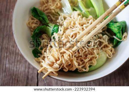 Close up of a bowl with noodle soup. Chopsticks are beside the bowl. - stock photo