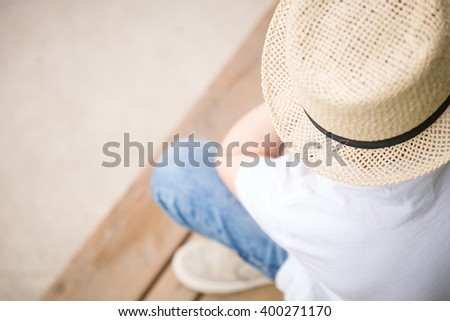 Close-up of a boy in a straw hat sitting on the wooden bench - view from the top. Vacation concept. outdoors. summertime.