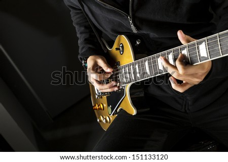 Close up of a boy playing a electric guitar. - stock photo