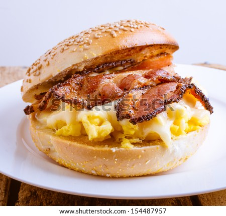 Close up of a breakfast sandwich of toasted sesame bagel, slab bacon, egg and melted cheese.