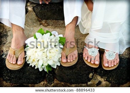 Close up of a bride and groom's feet and bouquet. They had just gotten married on the beach and are wearing sandals. - stock photo