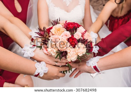 Close-up of a bride and her bridesmaids holding beautiful wedding bouquet. - stock photo