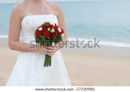 Close-up of a bride holding a beautiful bouquet at the beach. - stock photo