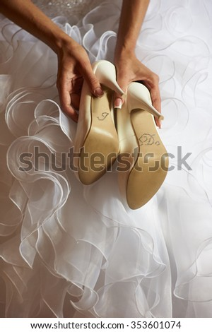 "close-up of a bride with wedding shoes in hes hands. At the bottom of it says ""I DO"" with small diamonds. Bride is dressed in white wedding dress."