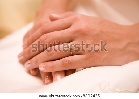 close up of a brides hands showing a diamond ring and unique manicure - stock photo