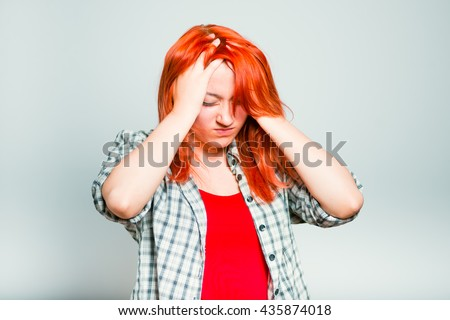 close-up of a bright red-haired girl has a headache, migraine - stock photo