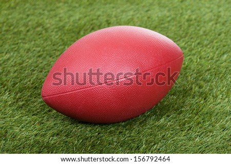 Close-up Of A Brown Rugby Bowl On Green Pitch - stock photo