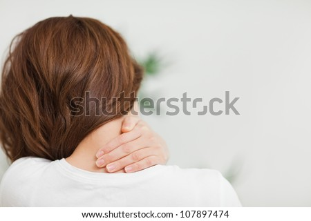 Close up of a brunette woman massing her neck in a room - stock photo