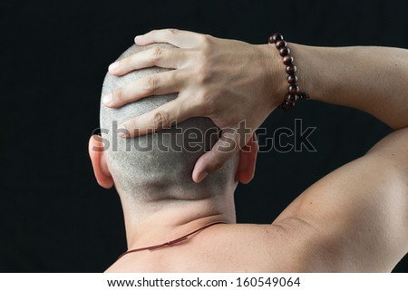 Close-up of a buddhist man wearing a mala feeling his newly shaved head, shirtless and shot from behind. - stock photo