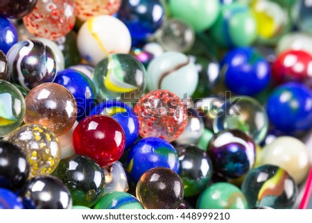 close up of a bunch of marbles in different colors for a background or texture - stock photo