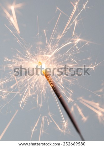 Close up of a burning sparkler on a grey background - stock photo