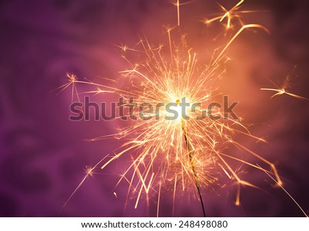Close up of a burning sparkler on a vibrant background - stock photo
