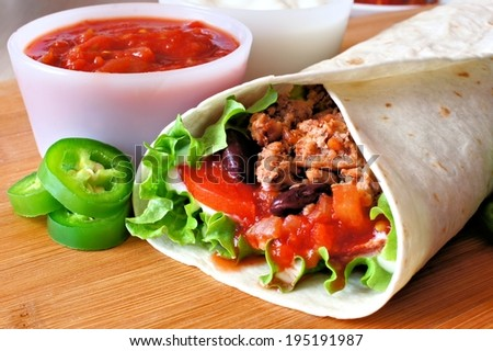 Close up of a burrito filled with meat and vegetables