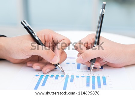 Close-up of a business documents with graphs analyzed by business people - stock photo