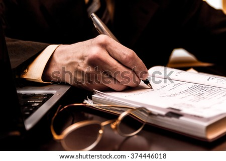 Close-up of a business man's hand write information in diary with blurred goggles in the foreground. - stock photo