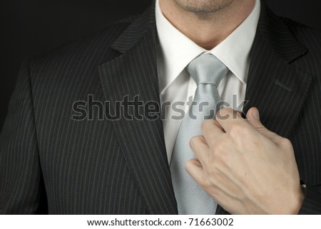 Close-up of a businessman adjusting his suit.