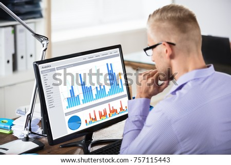 Close-up Of A Businessman Analyzing Business Graph On Computer In Office