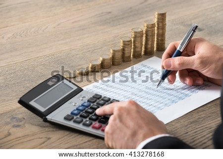 Close-up Of A Businessman Analyzing Financial Report With Stack Of Coins At Desk In Office