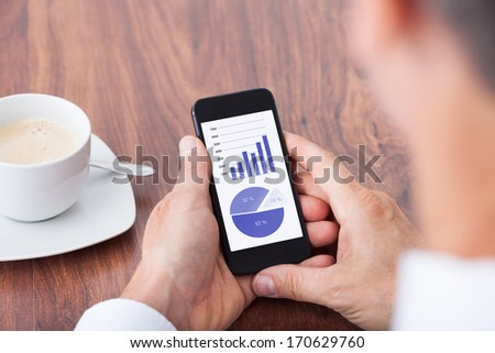 Close-up Of A Businessman Analyzing Graph On Cellphone - stock photo